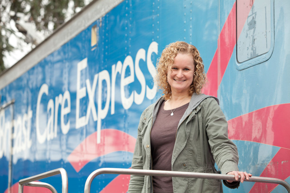 "A patient poses in from of the ""Breast Care Express"" mobile clinic"