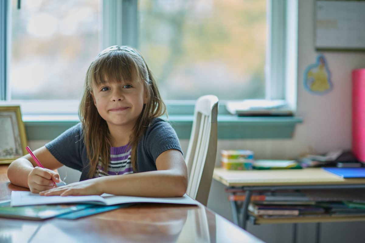 A young girl does her homework at the kitchen table.