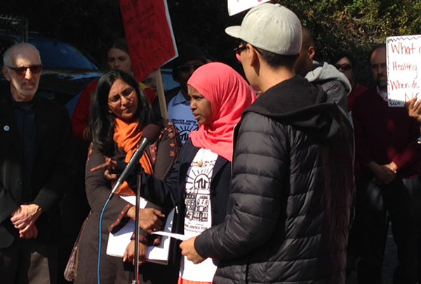 Sahro Farah stands at the microphone at a press conference outside of her apartment building.
