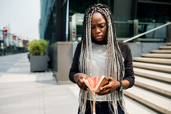 A young black woman looks at her wallet