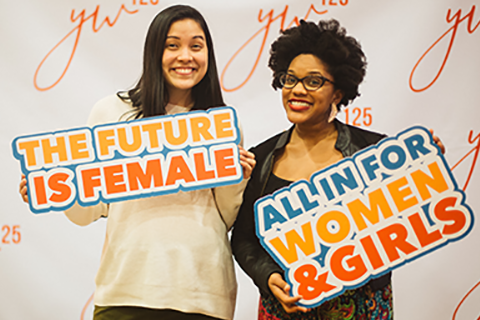 "Two women holding signs that say ""The future is female"" and ""all in for women and girls"""