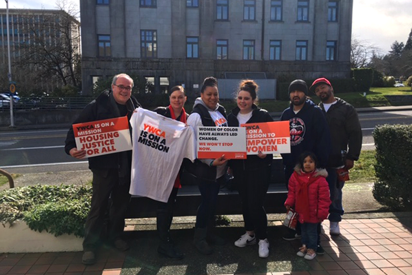Advocates stand with YWCA signs and t-shirts