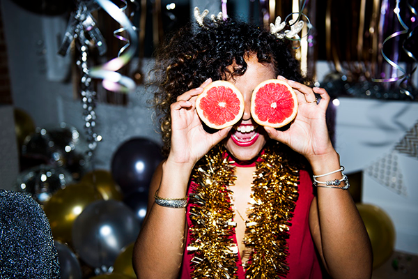 Black woman at party using grapefruit as glasses