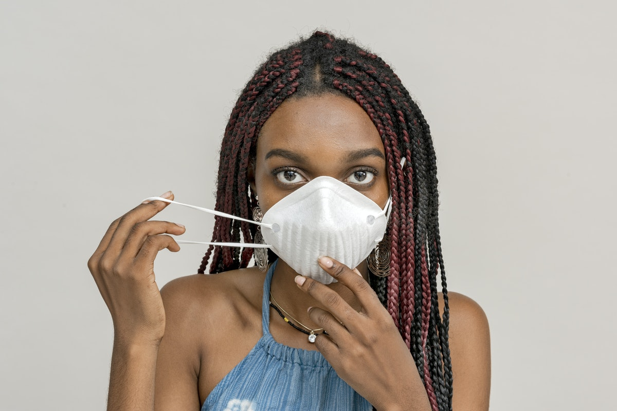 A Black woman puts on a face mask