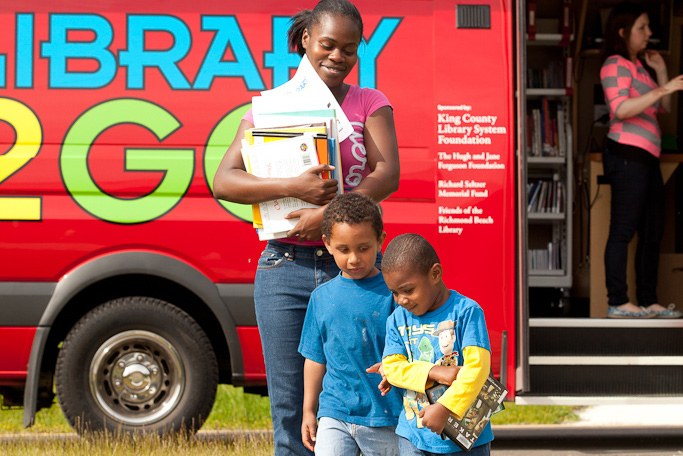 A mom and her sons walk back from a mobile library at YWCA's Passage Point location