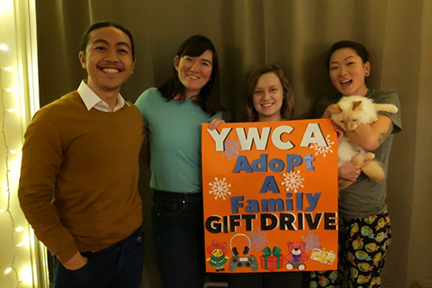 "Adopt a family donors posing with a sign that says ""YWCA adopt a family gift drive"""