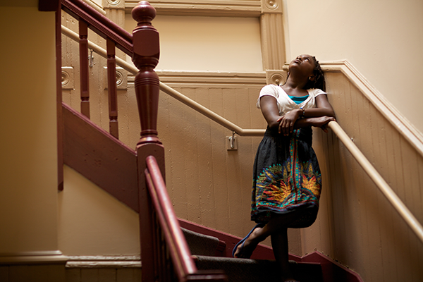 A young Black girl looking up a staircase