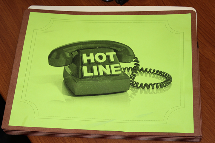"A folder with the word ""hotline"" printed on it is shown."