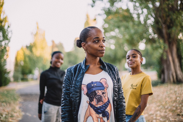 A Black woman stands with her two daughters