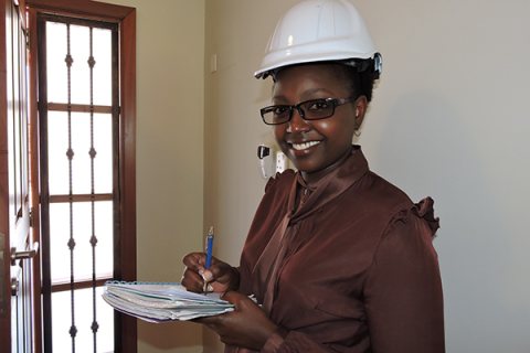 A woman in a hardhat holds an engineering inspection list