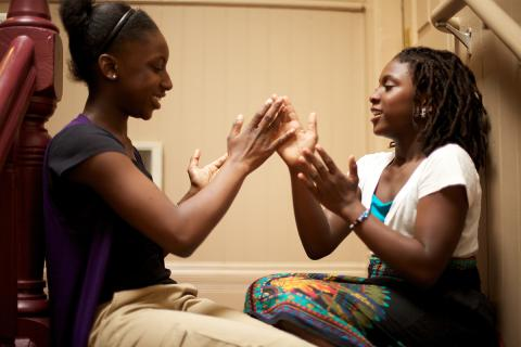 Two Black girls play a hand-clapping game in their stairwell