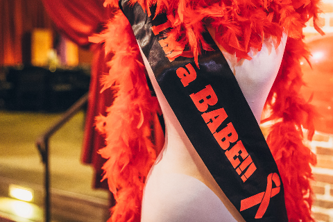 "Mannequin wearing a boa and sash that says ""I'm a BABE!!"""