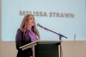 "Picture of client speaker on stage with ""Melissa Strawn"" on projector screen behind her"