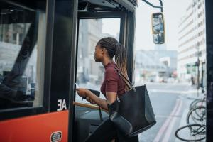 A black woman boards a city bus